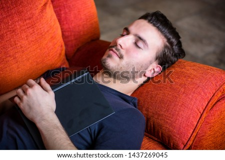 Over-worked, tired young man at home sleeping instead of working or studying, resting with open book on his chest