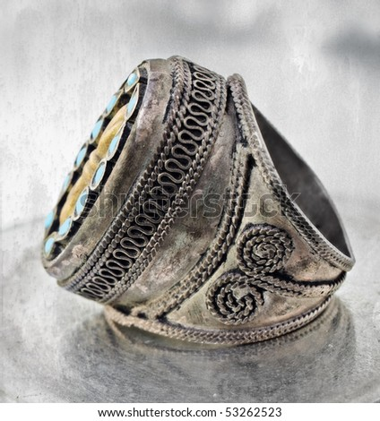 over 100 years old antique Turkish tribal ring with grunge pattern and blue stones on textured background