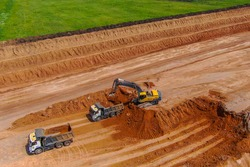 overburden works. Clay mining. excavator breaks up the topsoil to extract clay and loads into grey truck.drone photo. aerial view