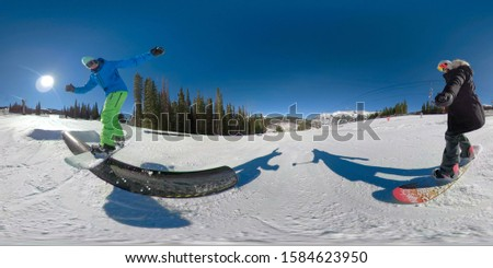 OVERCAPTURE, LENS FLARE, SELFIE: Cool shot of a male snowboarder sliding along a metal pipe in a fun park in the mountains of Colorado. Freestyle snowboarders ride and do tricks in a terrain park. #1584623950