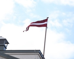 Overcast sky view of red and white colored Latvia national country flag floating n the mast. Photo taken on a warm summer day with overcast sky.