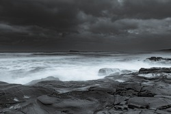 Overcast sunrise at the seaside in black and white from Birdie Beach on the Central Coast of NSW, Australia.