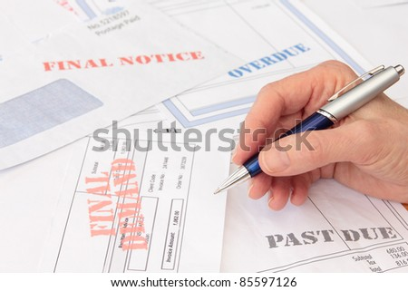 Overdue Bills and Invoices with Pen in Hand - stock photo