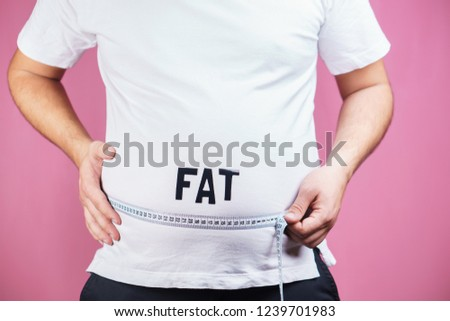 overeating, diet, glutton, diabetes, junk food. fat obese man with big belly and measuring tape