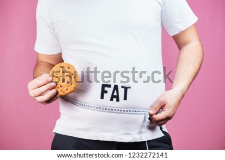 overeating, glutton, sugar addiction, junk food. Fat obese man with burger and measure tape