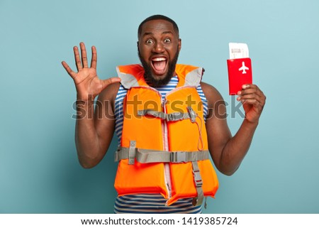 Overemotive dark skinned man shouts emotionally, keeps palm raised, reacts on unexpected journey, holds passport with tickets, wears lifejacket. People, emotions, traveling, lifestyle concept #1419385724