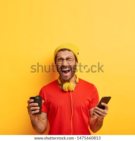 Overemotive positive man laughs from funny content publication, poses indoors with smartphone and disposable cup of coffee, keeps mouth wide opened, wears bright vivid clothes, isolated on yellow wall #1475660813