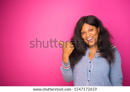 OVEREXCITED AFRICAN GIRL GIVEN DIRECTION FOR ADVERT USING FINGERS, YOUNG BLACK GIRL POINTING TO FREE SPACE. ADVERT CONCEPT