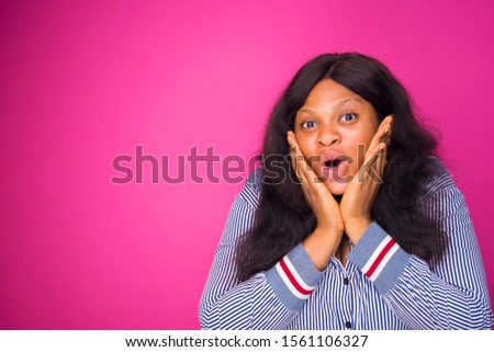 overexcited young African woman putting her hand on her Face after receiving a surprise and shocking news