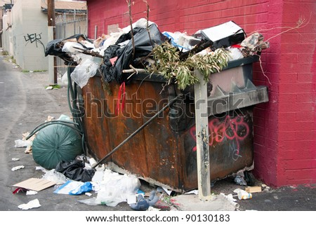 overfilled trash dumpster in ghetto neigborhood