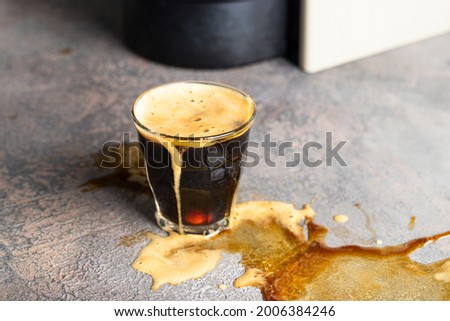 Overflow cup of coffee on concrete background. Foto stock ©