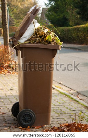 Overflowing brown garbage bin or can full with dead autumn leaves and plants