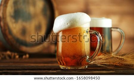 Overflowing foam head from beer glass pint, placed on wood Foto stock ©