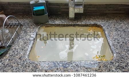 Overflowing kitchen sink, clogged drain.