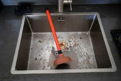 Overflowing kitchen sink, clogged drain. Plunger (force cup) in the sink. Plumbing problems.