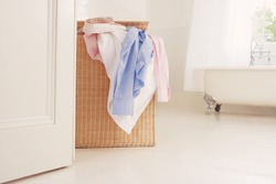 Overflowing wicker laundry basket in bathroom