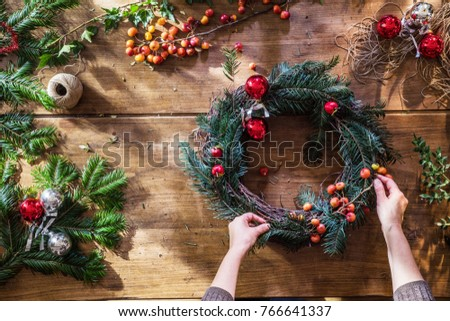 Overhead. Christmas time. On the wooden table, woman's hands make a crown for the festive season. branches of fir, berries, balls and rope to decorate it #766641337