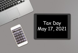 Overhead clean grey desk for laptop, smartphone and tablet computer with message for tax day 2021 as May 17