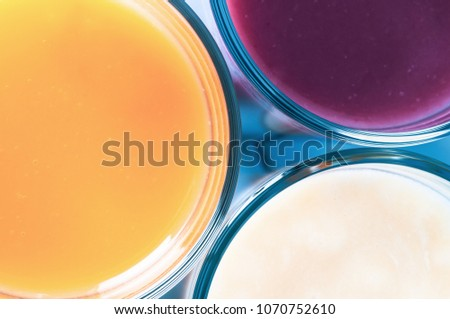Overhead close up of three different fruit flavoured smoothies in glasses. Filtered for retro effect. #1070752610
