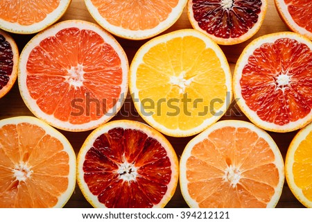 Overhead, closeup view of different color grapefruits and citrus fruit arranged artistically on a wooden table.