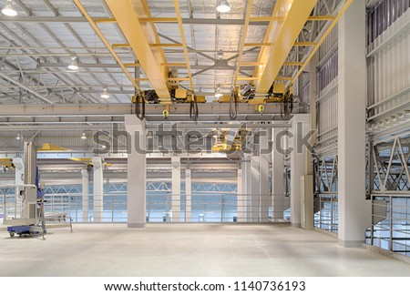 Overhead crane and concrete floor inside factory building for background. #1140736193