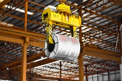 Overhead crane lift up steel coil with tong in wearhouse. Steel coils handling equipment. Steel warehouse and logistics operations.