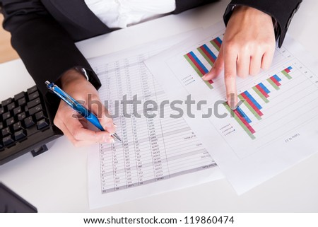 Overhead cropped image of female hands working with bar graphs and a spread sheet as she analyses data