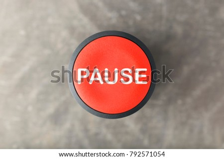 Overhead of a red pause push button over a blurred gray background