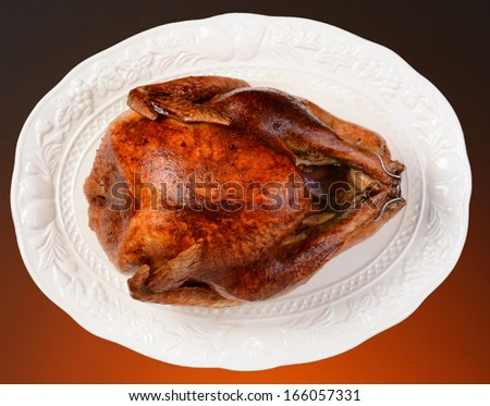 Overhead of a roasted Thanksgiving turkey on a white platter. Horizontal format on a light to dark warm background.