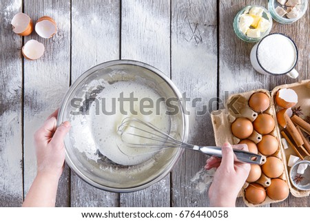 Overhead of baker hands whisking egg-white, copy space. Cooking ingredients for pastry on sprinkled with floor rustic wood, culinary classes or recipe concept. #676440058
