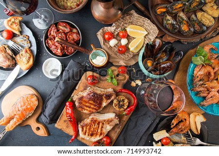 Overhead of dinner table. Barbecue meat and seafood with vegetable. Pork grilled steaks, grilled salmon trout, mussels, shrimps, dried tomato, cherry tomato,  glass of  wine. Picnic bbq party concept. #714993742
