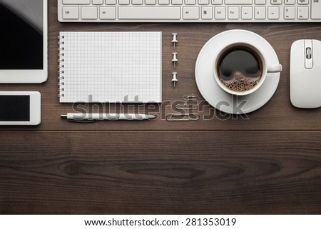 overhead of essential office objects in order on wooden desk with copy space