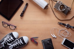 Overhead of essentials for modern young person. Different photography objects on wooden background: camera, smart phone, glasses, flashlight, digital tablet, wallet, watch, gumshoes, thermos