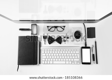 Overhead of essentials office objects in black and white./ Closeup of business objects in order on white desk.