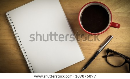 Overhead of notepad and pen and coffee on a desk