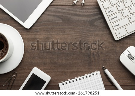 overhead of office table with notebook, computer keyboard and mouse, tablet pc and smartphone. copy space