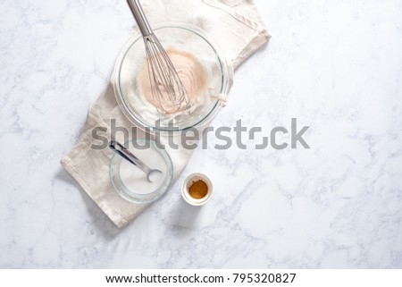 Overhead of powdered sugar glaze or icing in glass bowl with additional cream, cinnamon, and tablespoon elements.