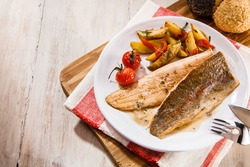 Overhead or high angle view on salmon trout fish fillet. Top down view of delicious barbecued fish meal on rustic background with copy space.