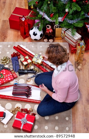 Overhead photo of a woman sat on a rug at home wrapping her Christmas presents. The teddy is generic and is not a brand bear.