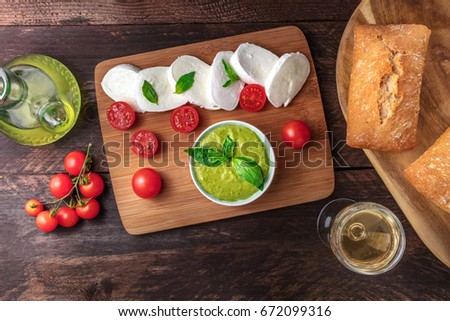 Overhead photo of buffalo mozzarella cheese with cherry tomatoes, basil leaves, ingredients of Caprese salad, glass of white wine, pesto sauce, olive oil, ciabattas, on rustic texture with copy space