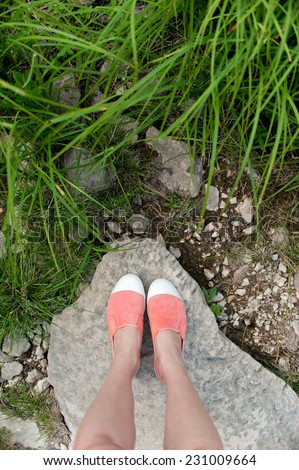 Overhead photo of feet on a background of big stone and grass. Women feets view from above. Exploring, travelling, tourism, leisure.