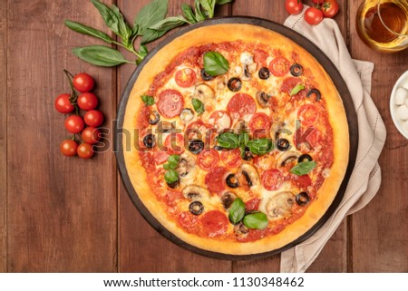 Overhead photo of pepperoni pizza with glass of white wine, cherry tomatoes and fresh basil leaves, shot from above on dark rustic background with place for text