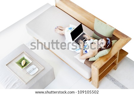 Overhead photograph of beautiful young woman using laptop at home sitting on sofa