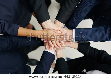 Overhead picture of group of business people joining hands