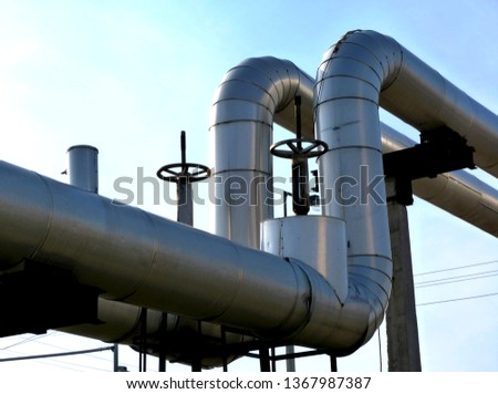 overhead pipeline abstract with elevation  change loop of aluminum shroud covered thick heating pipes on concrete support column under blue sky with valves & locks. electrical wires in the background stock photo
