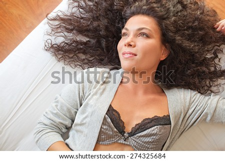 Overhead portrait of a beautiful young exotic woman relaxing on a bed at home, wearing sexy lingerie, interior space. Healthy wellness and well being living aspirational lifestyle, bedroom indoors.