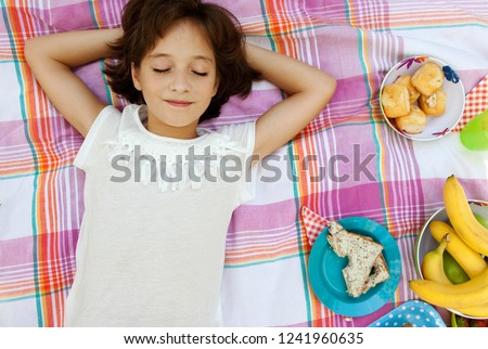 Overhead portrait of beautiful child girl laying on blanket having picnic food, relaxing smiling with eyes closed, outdoors. Fruit and sandwiches fun healthy eating, leisure recreation lifestyle.