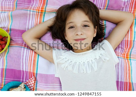 Overhead portrait of beautiful hispanic child girl laying on blanket having picnic food, relaxing smiling and looking, outdoors. Fruit and fun healthy eating, leisure recreation lifestyle.