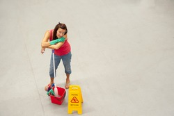 Overhead portrait of female business cleaner with mob, bucket and 'Caution Wet Floor'-Sign on warehouse floor and copy space.