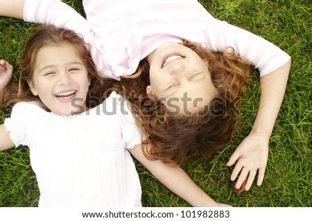 Overhead portrait of two girls laying down on green grass, laughing.